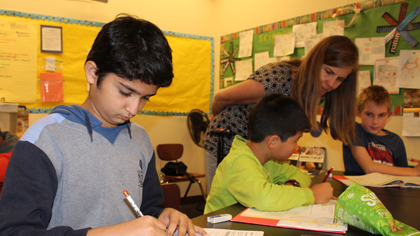 Students working and teacher assisting one student