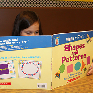 "Elementary school student reading book titled ""Math=Fun! Shapes and Patterns""."