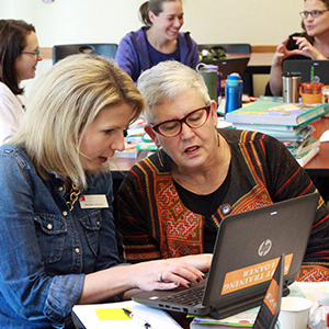 Two staff members work together on a laptop computer