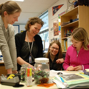 An elementary school principal and three teachers work together in a classroom