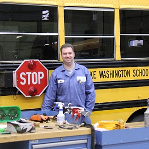 LWSD chool bus mechanic with tools and supplies in front of a school bus