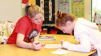 Elementary School teacher working with student across table