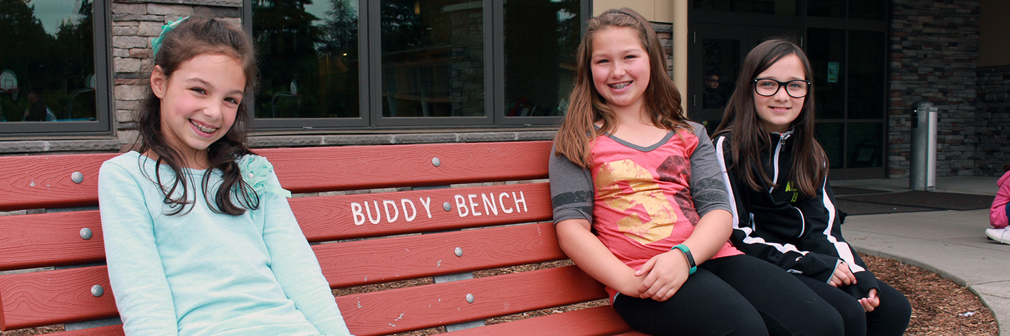 "Three students sitting on a ""Buddy Bench"""