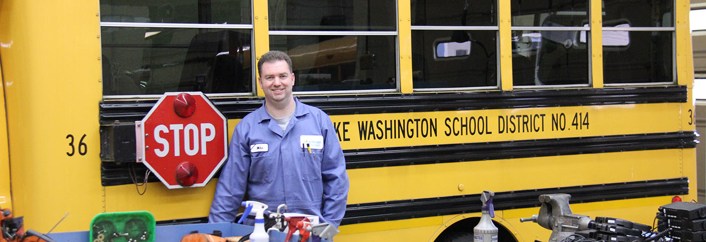 Bus mechanic standing in front of a school bus.