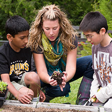 Two male students and a female teacher kneeling on the ground looking at plants.