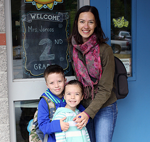 "Mother with two children in front of sign that says ""Welcome Mrs. Jaross 2nd Grade"""