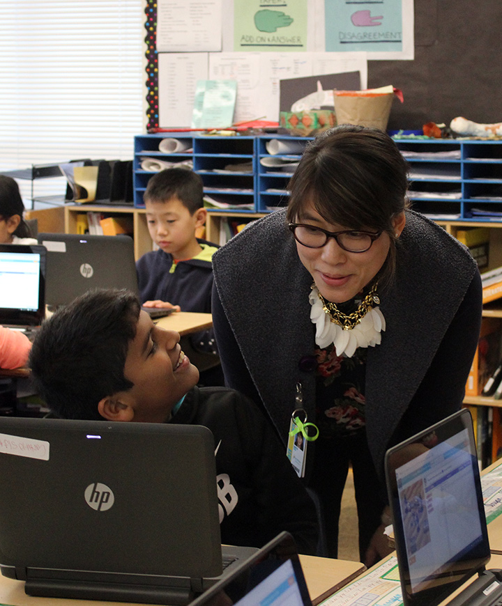 Smiling student behind laptop looks up at teacher, who is bending down toward him