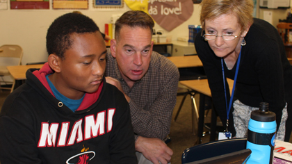 Two staff members assisting a student wearing a Miami Heat sweatshirt, all looking at a laptop