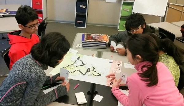 Students playing a board game they created.