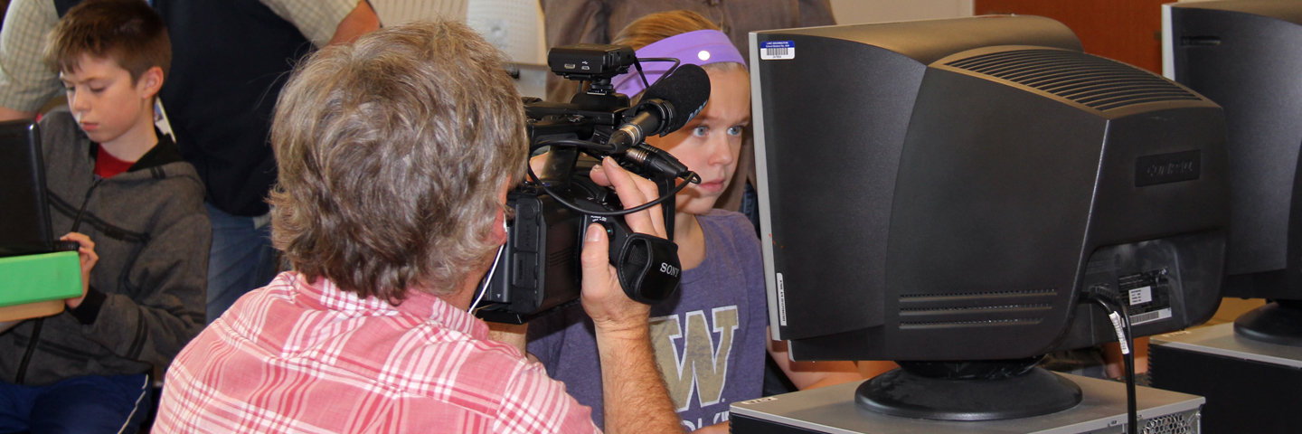 Videographer taking video footage of student using a computer.