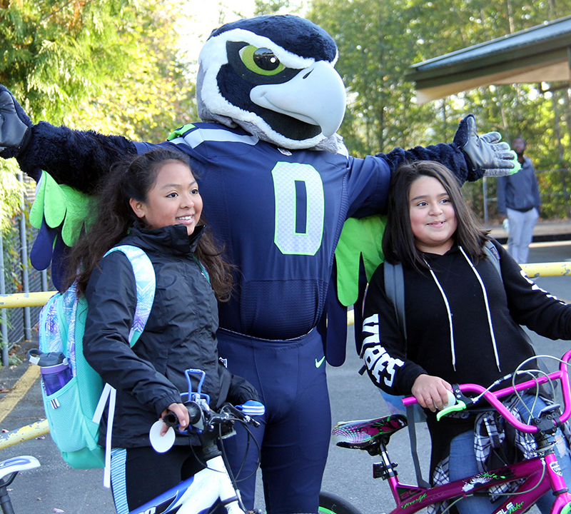 Two Eintein students who biked to school take a photo with Blitz the Seahawk