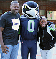 A student and her dad take a photo with Blitz the Seahawk