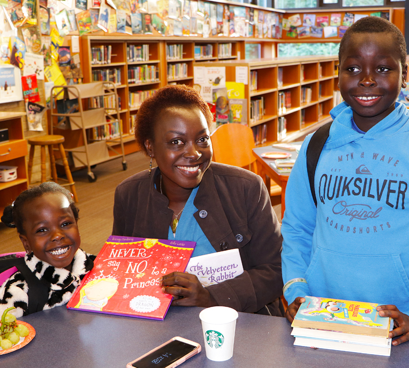 Mom and two children read together while enjoying dougnuts and fruit in the Muir library.