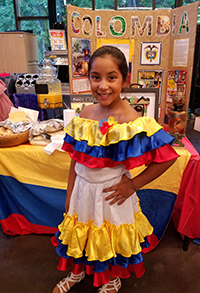 Student wears traditional clothing from Colombia in front of display about the country
