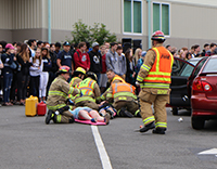 Emergency personnel treat pretend injuries during a mock car crash demonstration