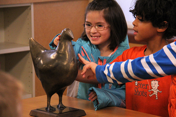 First-graders smiling and touching a bronze chicken sculpture.