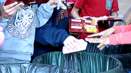 Students separating their trash, compost, and recycleable items