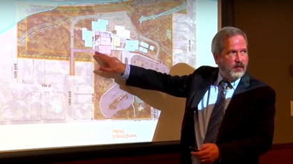 Man presenting, pointing to map of where new school will be