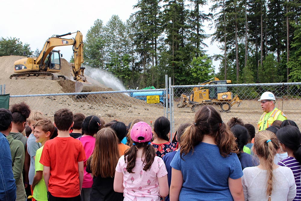 Students watch an excavator and bulldozer from their playground.