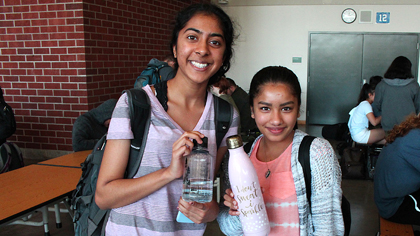 Two students show their reusable water bottles