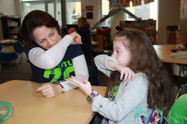 A nurse teaching a student to sneeze into her sleeve.