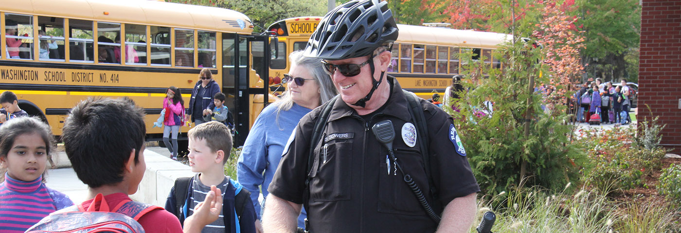 Police officer talks with students as they leave school.