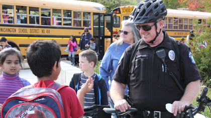 Police officer talks with students as they leave school