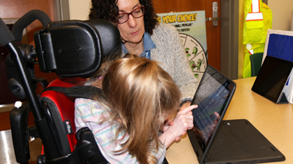 Occupational Therapist working with elementary student on asisstive technology laptop