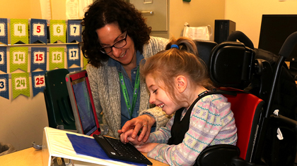 Occupational Therapist working with an elementary student on an assistive technology iPad and keyboard