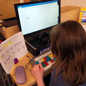 Elementary school student works on assistive technology keyboard