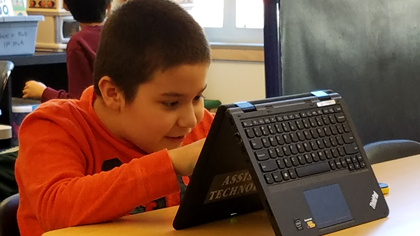 Elementary student works on assistive technology laptop