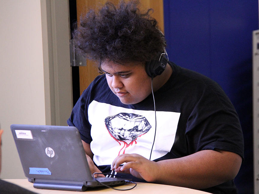Student wearing headphones while typing on a laptop computer