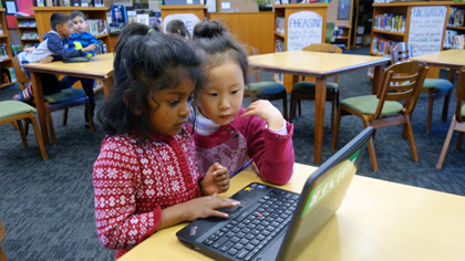 Two early elementary students working together on a laptop