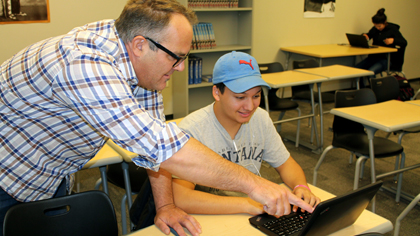 Staff member assisting high school student with work on a laptop