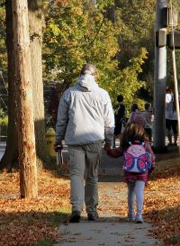 adult and child walking to school