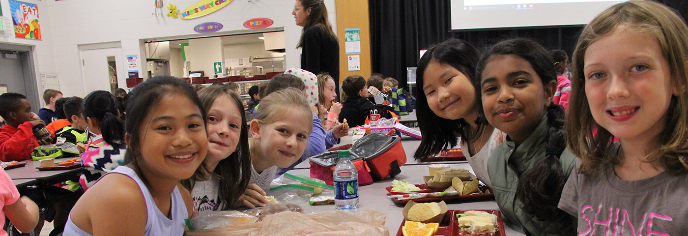 Elementary girls sitting at a table and smiling during lunch.