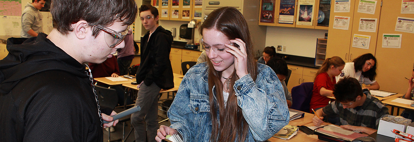 Students in safety goggles examining something
