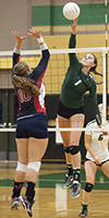 Redmond High School volleyball team member hits the ball during a game with other team attempts to block it