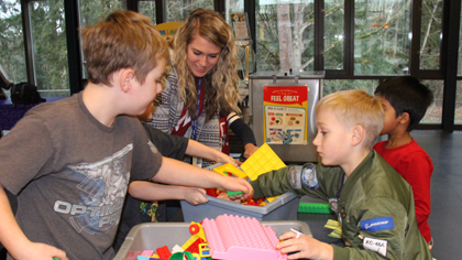 Students and instructional assistant play with Legos in after school care program