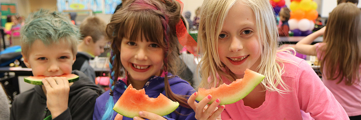 Three elementary students eating watermelon in the cafeteria at lunch.