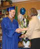 Emerson K-12 graduate receives his diploma from a staff member