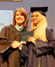Tesla STEM High School student receives her diploma from a staff member